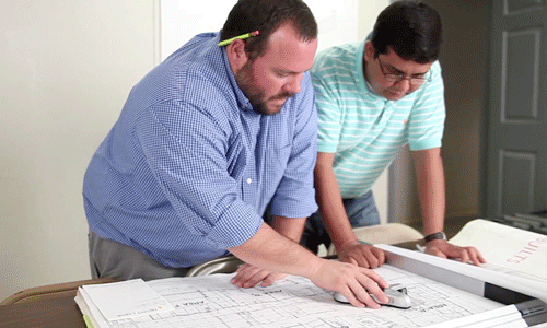 two people discussing a blueprint